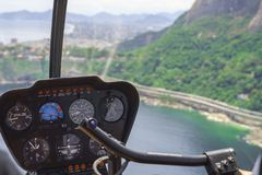 从一次直升机驾驶舱飞行的看法在里约热内卢 与仪表盘的驾驶舱 上尉在飞机座舱内 免版税库存照片