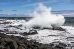 从一残破的美丽的飞溅在火山岩波浪 免版税库存图片