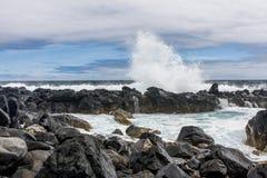 从一残破的美丽的飞溅在火山岩波浪 库存照片