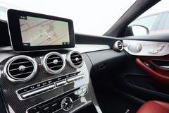 从一辆汽车里边的看法在仪表板和在汽车前面的被弄脏的街道的零件与航海单位的 免版税库存照片