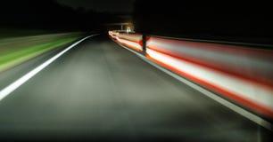 从一辆移动的汽车的看法在一条车道的高速公路,在一条被更新的路 停机拦截网从边是可看见的 库存照片