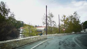 从一辆移动的汽车的看法在有房子、鳟鱼和路标的一条狭窄的街道上在雨以后的一阴天 E 影视素材