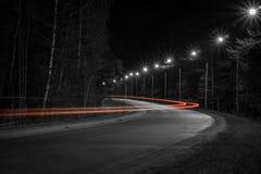 从一辆通过的汽车的车灯的轨道在夜路的 库存照片