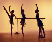 从三位年轻舞蹈家剪影的构成芭蕾的在橙色背景摆在 免版税库存照片
