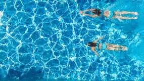 从上面游泳场水空中寄生虫视图的活跃女孩,孩子游泳,孩子获得乐趣热带家庭度假 免版税库存照片