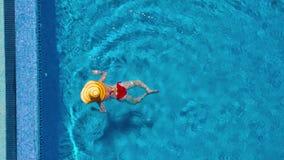从上面的看法作为红色泳装和一个大黄色帽子游泳的一名妇女在水池 股票视频