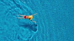 从上面的看法作为红色泳装和一个大黄色帽子游泳的一名妇女在水池 股票录像