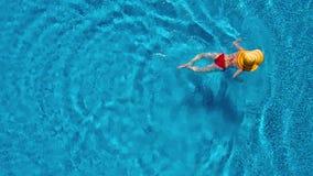 从上面的看法作为红色泳装和一个大黄色帽子游泳的一名妇女在水池 影视素材