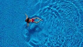 从上面的看法,红色泳装的一名妇女在水池游泳 股票视频
