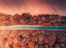 从上面移动在秋天森林里的汽车 库存照片