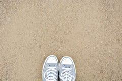 从上面站立与在沙子的两双鞋子 库存图片