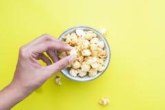 从上面被观看的玉米花碗,顶视图妇女喜欢吃popc 图库摄影