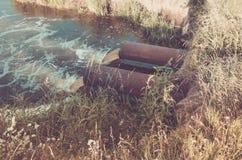 从下水道的污水污染涌出从下水道的湖/水到河 ??? 免版税库存图片
