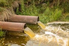 从下水道的污水污染涌出从下水道的湖/水到河 免版税库存照片