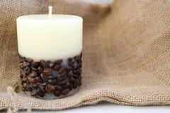 从下面给与没有味道的灯芯的美好的轻的米黄蜡烛打蜡装饰用在老棕色帆布背景的咖啡豆  免版税库存图片