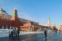 从不同的国家的游人沿红场走在列宁` s陵墓和克里姆林宫墙壁附近 免版税图库摄影