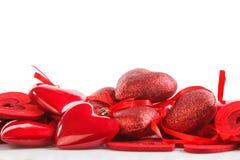 从不同的材料与丝带,在一张白色桌上的谎言的红色心脏 免版税库存照片