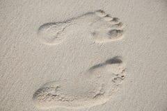 从两个脚印的顶视图在沙子地面 库存照片