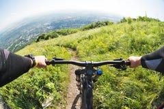 从乘坐下坡从一座高山的骑自行车者的第一个人的看法在一个城市的背景中距离的 免版税库存图片