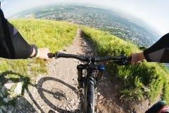 从乘坐下坡从一座高山的骑自行车者的第一个人的看法在一个城市的背景中距离的 库存图片