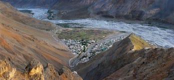 从了不起的高度的照片在Spiti谷:在河附近有小山村,峭壁由日落光芒点燃 免版税库存照片
