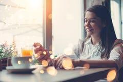 从互联网的微笑的妇女读书新闻使用手机,在咖啡馆的早餐 库存图片