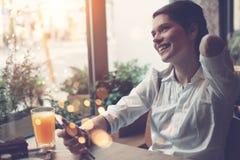 从互联网的微笑的妇女读书新闻使用智能手机,在咖啡馆的早餐 库存图片