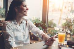 从互联网的微笑的英俊的妇女读书新闻使用手机,在咖啡馆的早餐 库存图片
