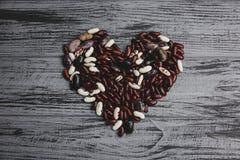 从五颜六色的扁豆的心脏在一张木桌上 免版税库存图片