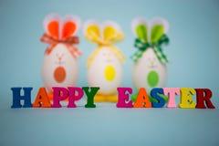 从五颜六色的木信件的愉快的复活节文本用以逗人喜爱的兔宝宝的形式滑稽的鸡蛋在蓝色背景 免版税库存图片