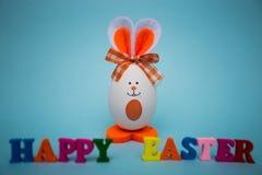 从五颜六色的木信件的愉快的复活节文本用以逗人喜爱的兔宝宝的形式滑稽的鸡蛋在蓝色背景 库存图片