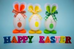 从五颜六色的木信件的愉快的复活节文本用滑稽的鸡蛋以逗人喜爱的兔宝宝的形式在蓝色背景的 库存照片
