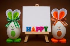 从五颜六色的木信件的愉快的文本在画架用以逗人喜爱的兔宝宝的形式滑稽的鸡蛋在棕色背景 库存照片