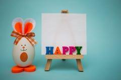 从五颜六色的木信件的愉快的文本在画架用滑稽的鸡蛋以逗人喜爱的兔宝宝的形式在蓝色背景的 免版税库存照片