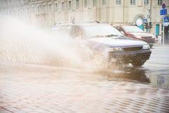 从从一个水坑的一辆蓝色汽车喷洒在路的雨中 图库摄影