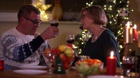 从他们的玻璃的成熟丈夫和妻子饮料红酒,当坐在与蜡烛时的一张被盖的桌上 一个人和  影视素材