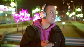 从他的智能手机的微笑的和笑的英俊的年轻人听的音乐在无线黑耳机,跳舞  影视素材