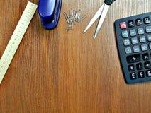 从企业背景计算器、统治者和其他细节上的一个另外的形式的看法在一张木桌上 免版税库存照片