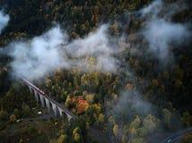 从低谷上的街道一个有薄雾的森林秋天、鸟瞰图飞行通过云彩与雾和树 免版税库存图片