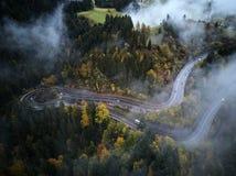 从低谷上的街道一个有薄雾的森林秋天、鸟瞰图飞行通过云彩与雾和树 免版税库存照片