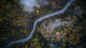 从低谷上的街道一个有薄雾的森林秋天、鸟瞰图飞行通过云彩与雾和树 库存照片