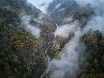 从低谷上的街道一个有薄雾的森林秋天、鸟瞰图飞行通过云彩与雾和树 库存图片