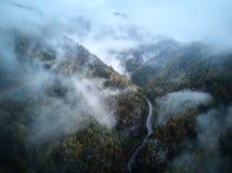 从低谷上的街道一个有薄雾的森林秋天、鸟瞰图飞行通过云彩与雾和树 图库摄影