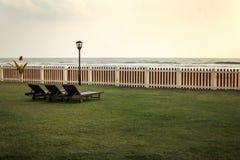 从倒空在绿色草坪,海滩的sunbeds的旅馆手段的看法和 免版税库存图片