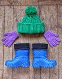 从儿童` s冬天辅助部件的滑稽的矮小的人:帽子,手套 免版税图库摄影