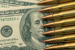 从军队机器宏指令的作战子弹在钞票$ 100 强的军队防御的概念和标志  库存照片