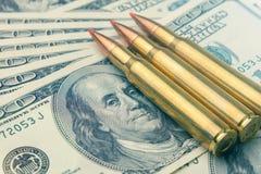 从军队机器宏指令的作战子弹在钞票$ 100 强的军队防御的概念和标志  图库摄影
