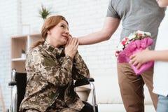 从军队返回的轮椅的妇女退伍军人 儿子和丈夫是愉快看她 免版税图库摄影