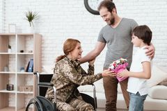 从军队返回的轮椅的妇女退伍军人 儿子和丈夫是愉快看她 库存照片