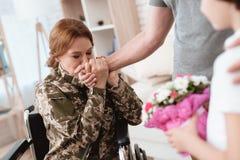 从军队返回的轮椅的妇女退伍军人 儿子和丈夫是愉快看她 库存图片